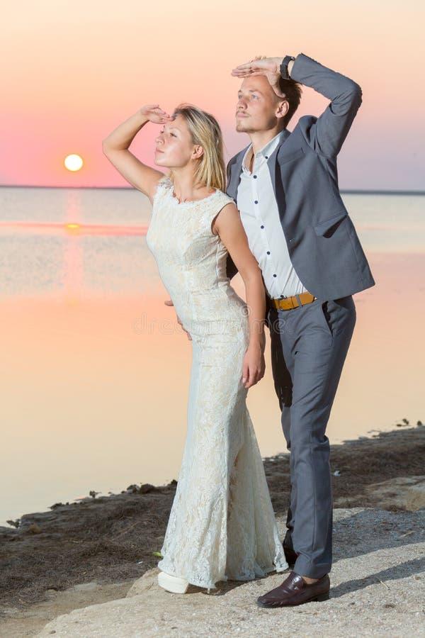 la sposa e lo sposo sono fotografati contro il contesto di un lago di sale basso che sorridono e che godono della loro nuova vita immagine stock libera da diritti