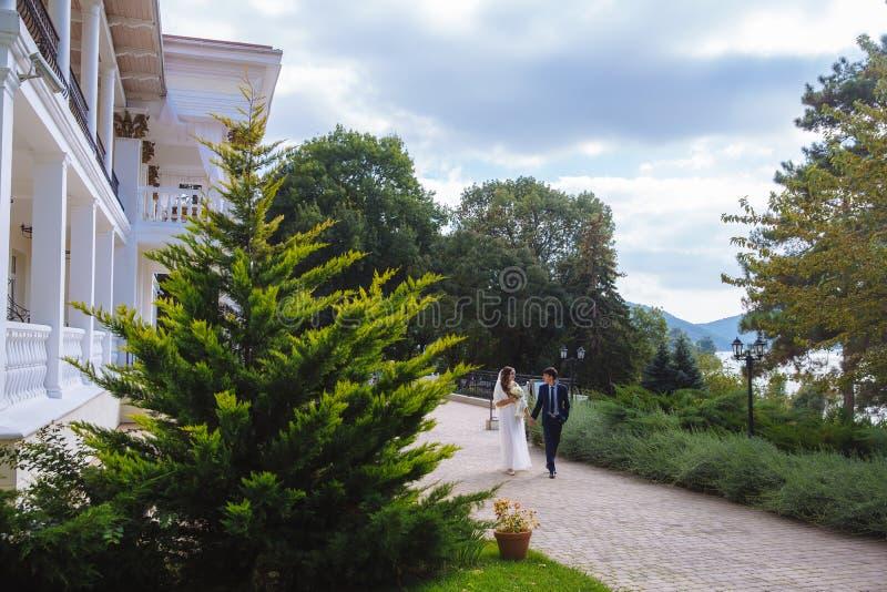 La sposa e lo sposo stanno camminando rapidamente lungo il park6 verde che conduce una conversazione entusiasta, discutere fotografia stock