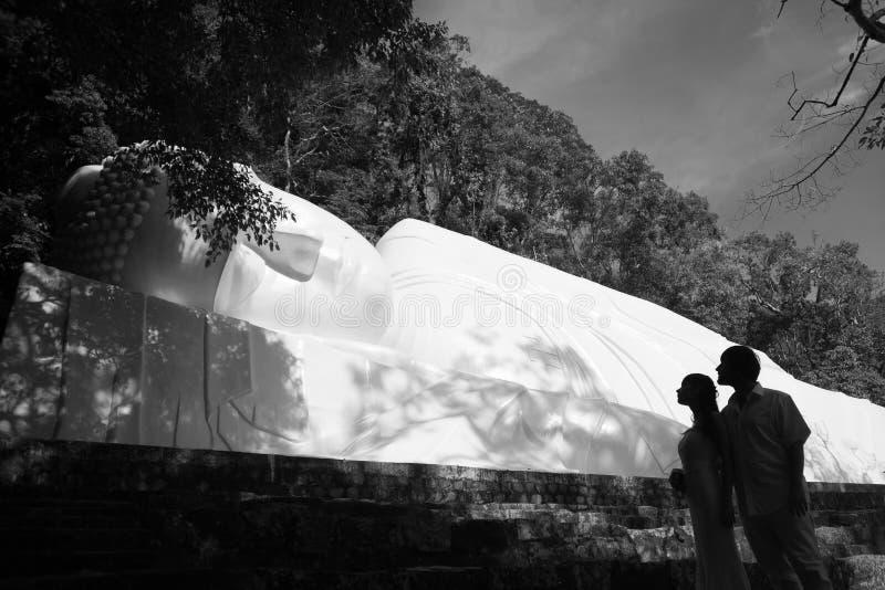 La sposa e lo sposo stanno contro un nirvana enorme Buddha nel Vietnam immagini stock libere da diritti
