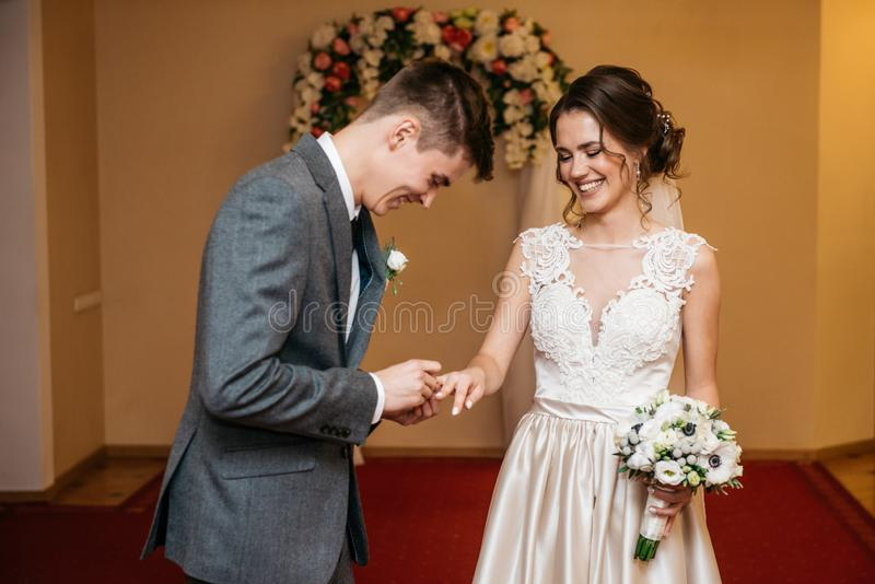 La sposa e lo sposo stanno scambiando le fedi nuziali nell'anagrafe fotografie stock libere da diritti