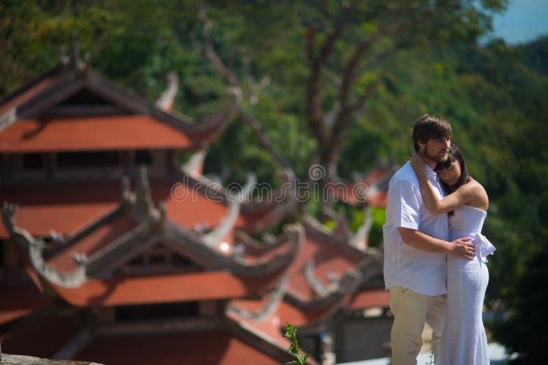 La sposa e lo sposo stanno sui precedenti di vecchio tempio cinese fotografia stock libera da diritti