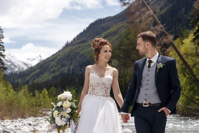La sposa e lo sposo sui precedenti di una torrente montano fotografia stock