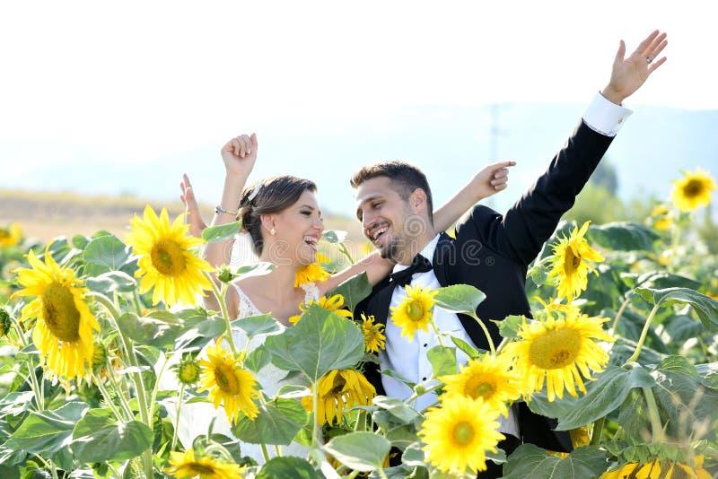 La sposa e lo sposo in una bella tenuta leggera abbracciano fotografia stock