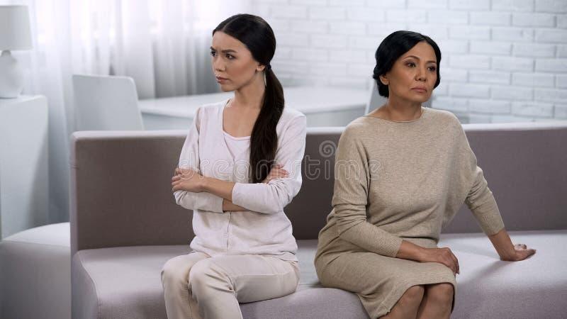 La sposa e la suocera nel litigio, tenente il silenzio, si siedono esclusivamente ed indietro fotografie stock libere da diritti
