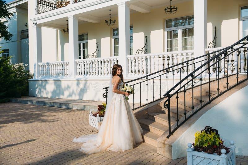 La sposa elegante con nozze fiorisce il mazzo, donna attraente in vestito da sposa La ragazza in un vestito bianco va immagine stock libera da diritti