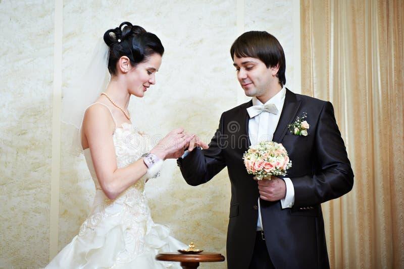 La sposa felice indossa la fede nuziale il suo sposo fotografia stock