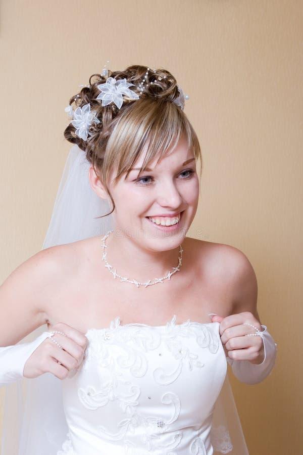 La sposa felice mette sopra il vestito fotografia stock libera da diritti