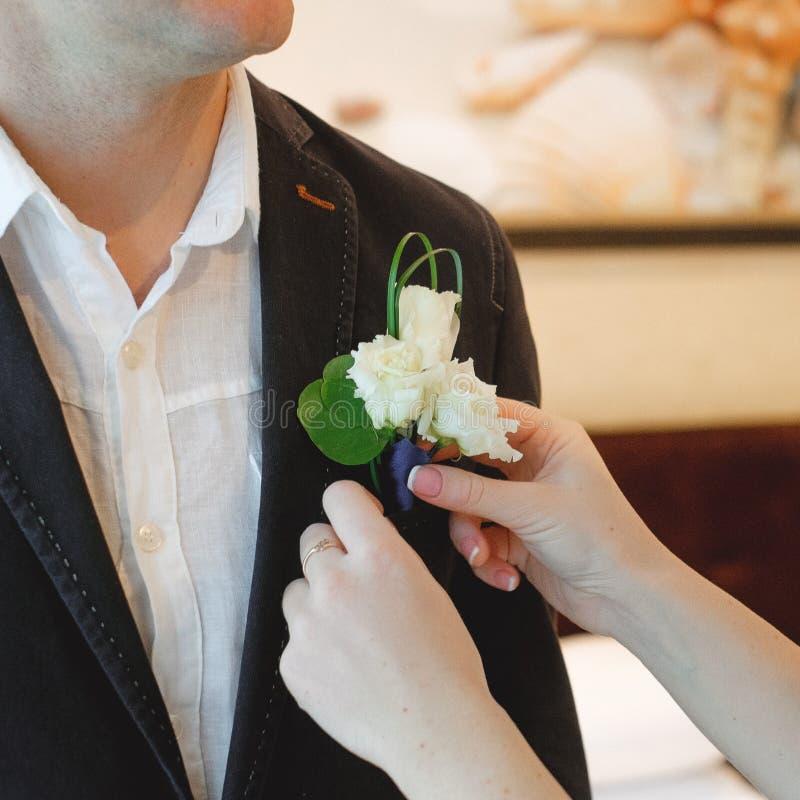 La sposa indossa un occhiello per lo sposo immagine stock libera da diritti