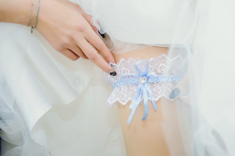 La sposa indossa una giarrettiera del pizzo - un accessorio di nozze fotografia stock