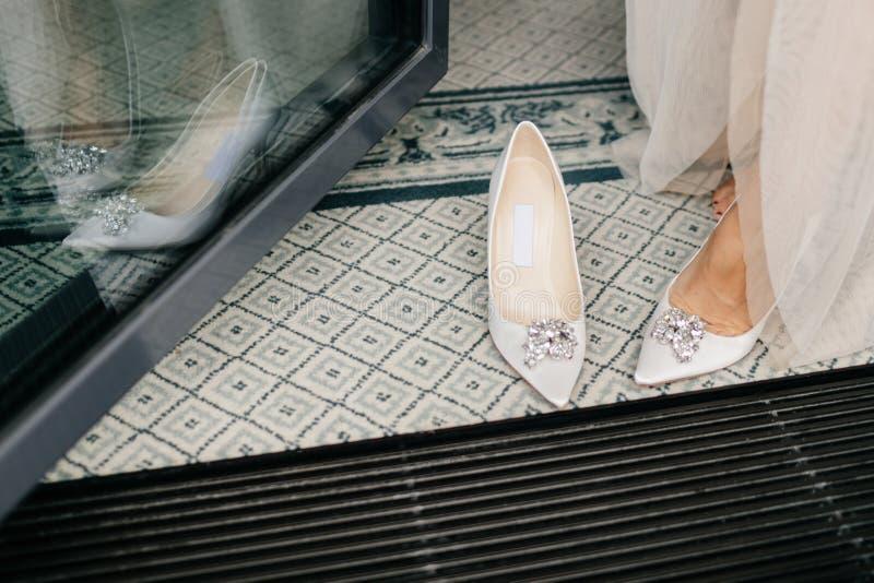La sposa irriconoscibile in vestito bianco, mette sopra le scarpe di nozze, ha piedi teneri, preparares per l'occasione speciale  fotografia stock