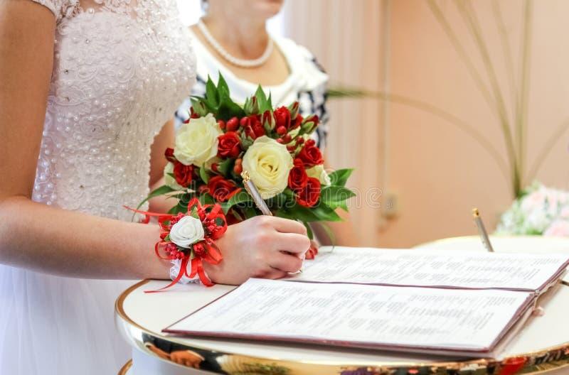 La sposa mette la firma nell'anagrafe fotografie stock libere da diritti