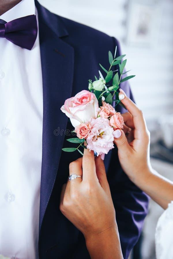 La sposa mette lo sposo sul boutonniere dalle rose sul giorno delle nozze immagini stock libere da diritti