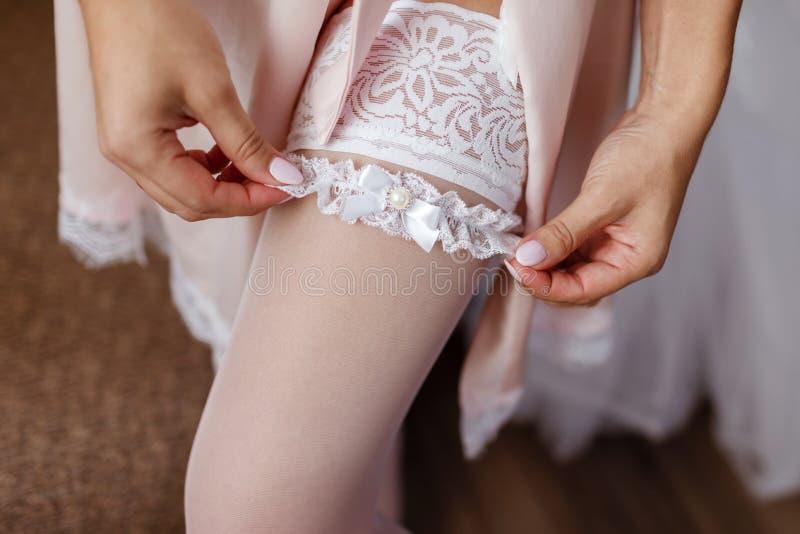 La sposa nel bianco mette sopra una bella fasciatura openwork su una gamba elegante Arco della stella blu con il nastro blu (invo fotografia stock