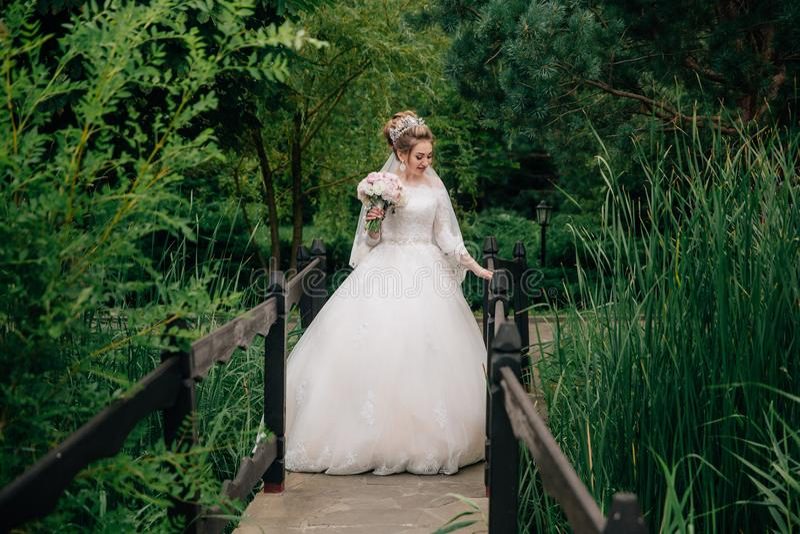 La sposa nell'abito di nozze sta stando all'inizio del ponte attraverso il fiume in una foresta verde la ragazza fotografia stock