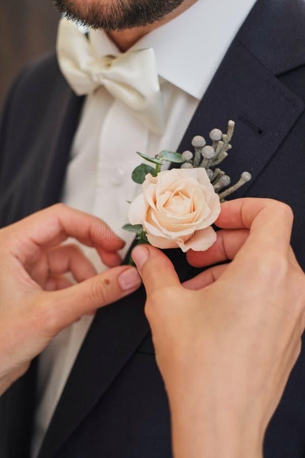 la sposa raddrizza il rosa del boutonniere dello sposo è aumentato immagini stock libere da diritti