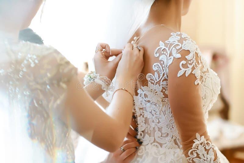 La sposa splendida e bionda in vestito di lusso bianco sta preparandosi per nozze Preparazioni di mattina Donna che mette sul ves immagini stock