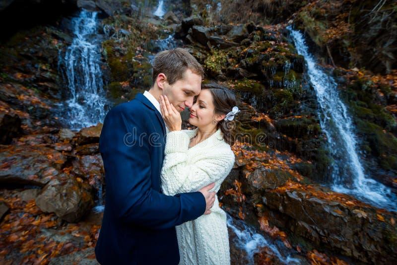 La sposa splendida tocca morbidamente il fronte del suo sposo Cascata su fondo Autunno in montagne fotografia stock