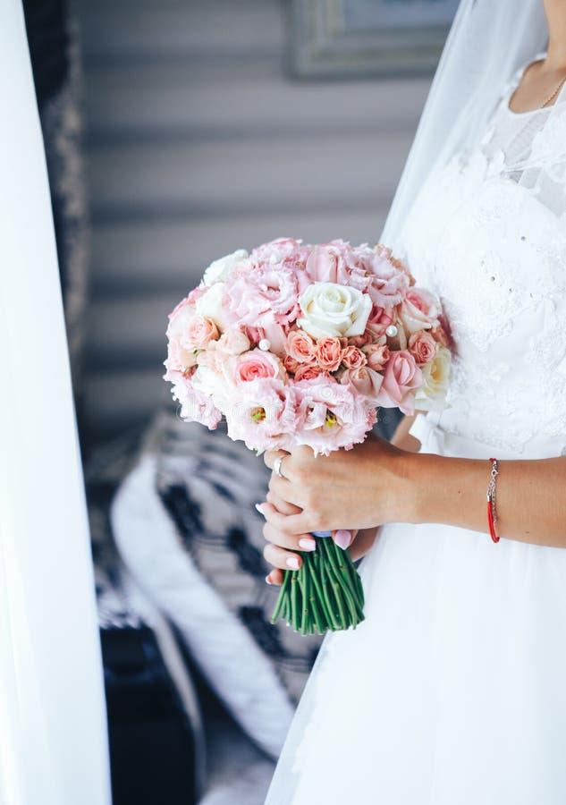 La sposa sta alla finestra e tiene un mazzo di nozze Primo piano fotografia stock