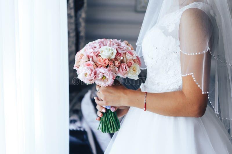 La sposa sta alla finestra e tiene un mazzo di nozze Primo piano immagini stock