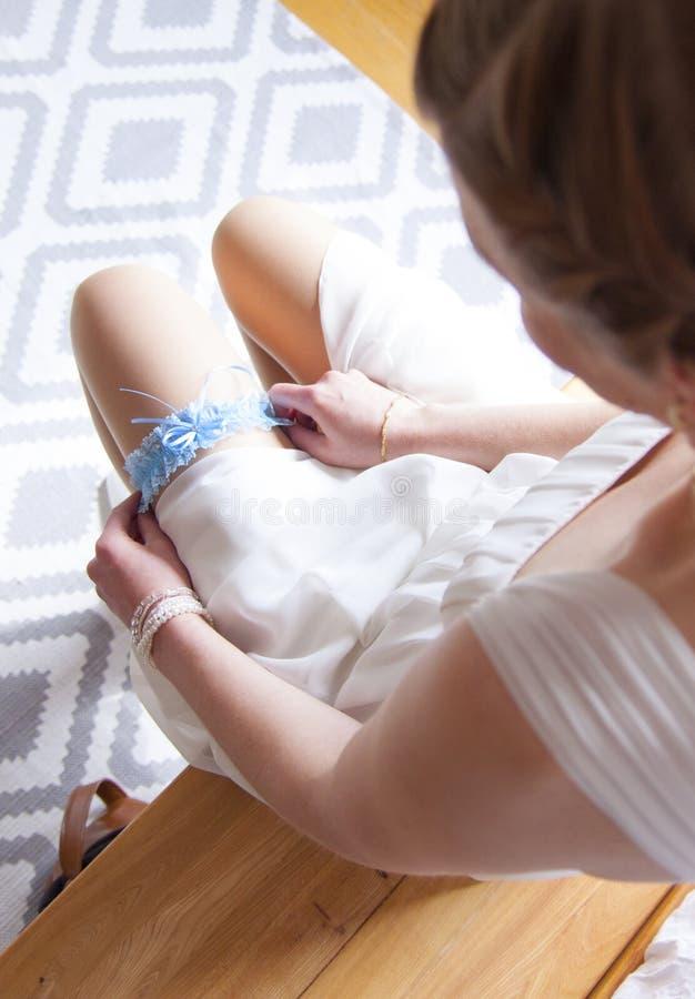 La sposa sta mettendo sulla giarrettiera immagine stock libera da diritti