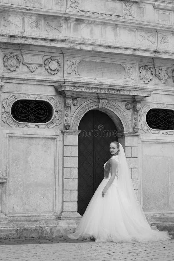 La sposa sta stando davanti alla costruzione fotografia stock