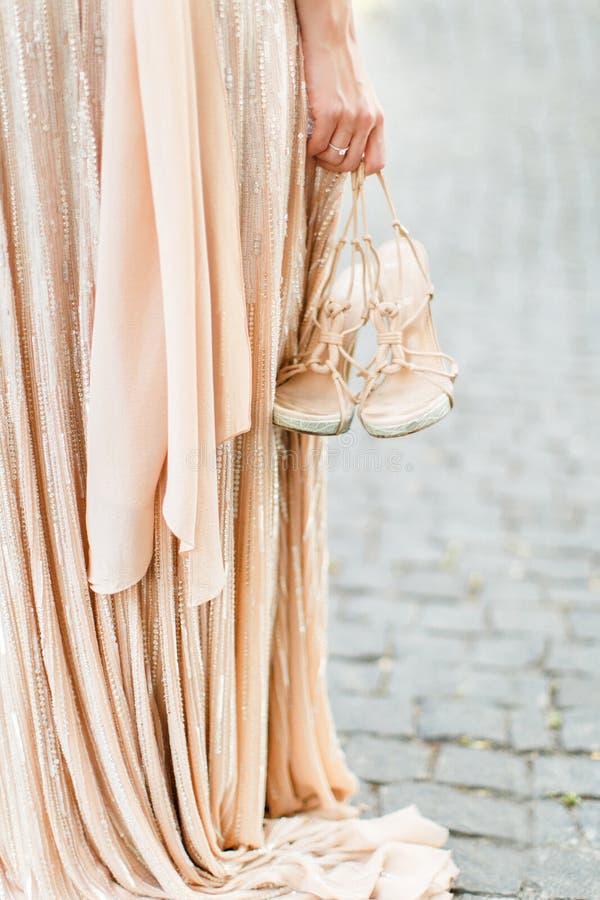 La sposa sta tenendo le scarpe in sua mano, scarpe di nozze Scarpe leggere nella mano di una ragazza fotografie stock