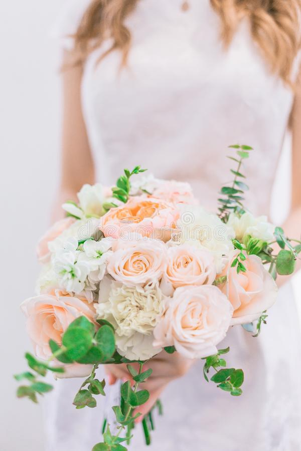 La sposa sta tenendo un mazzo splendido di nozze nei colori pastelli delle peonie e delle rose fotografia stock libera da diritti