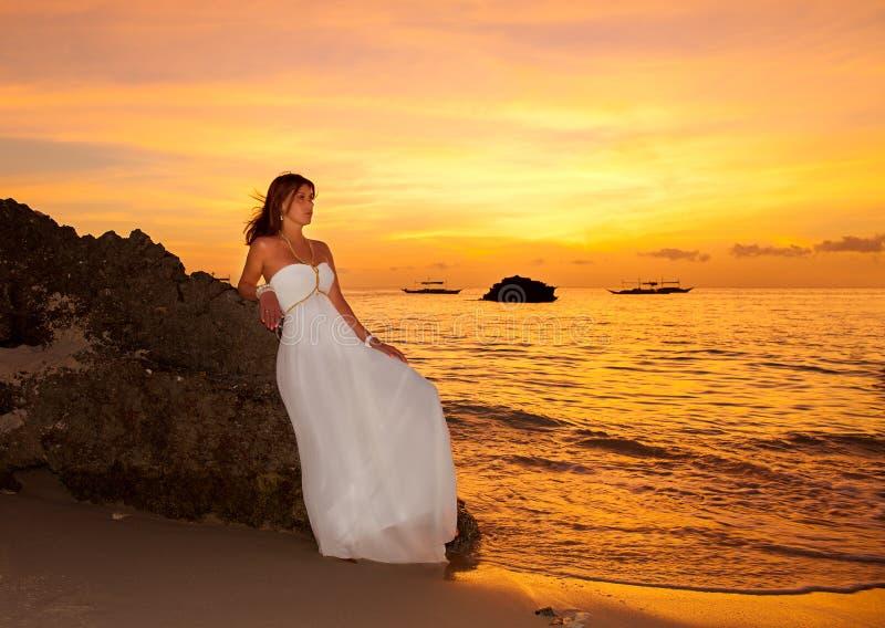 La sposa su una spiaggia tropicale con il tramonto nei precedenti immagini stock libere da diritti
