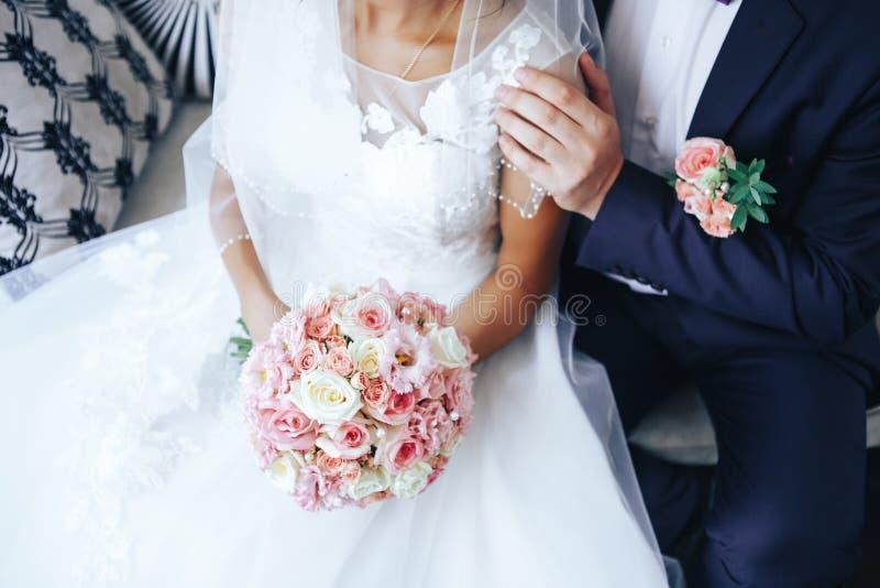 La sposa tiene insieme un mazzo di nozze in mani, lo sposo abbraccia la sua sposa  Concetto dell'amante di nozze Primo piano immagine stock libera da diritti