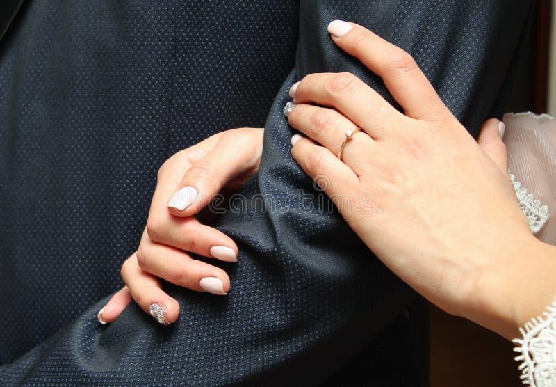 La sposa tiene la mano del ` s dello sposo fotografia stock