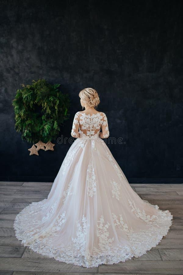 La sposa in un magnifico, bianco, vestito da sposa con un treno lungo immagine stock libera da diritti