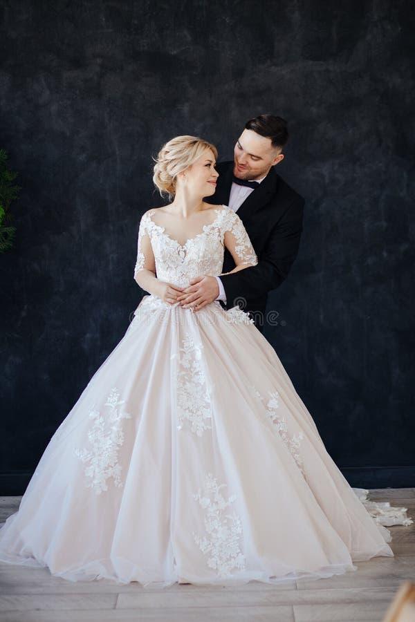 La sposa in un magnifico, bianco, vestito da sposa con un treno lungo immagini stock libere da diritti