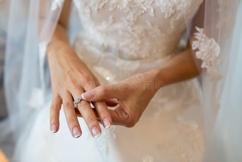 La sposa in un vestito da sposa con un velo che indossa un anello d'argento sul dito medio immagine stock libera da diritti