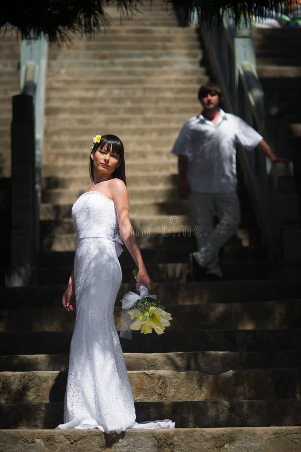 La sposa in un vestito da sposa elegante è sui precedenti di grande scala e dietro lei è lo sposo immagine stock