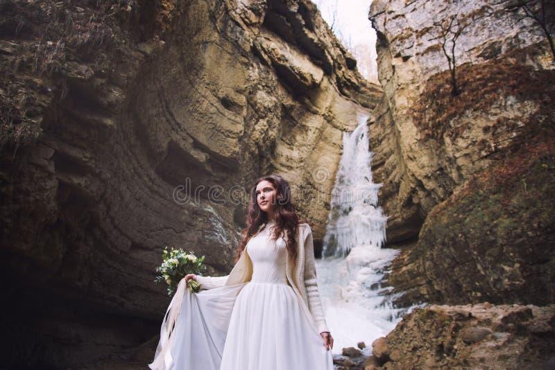 La sposa in un vestito da sposa elegante sta stando su un fondo di un ghiacciaio in una catena montuosa fotografia stock