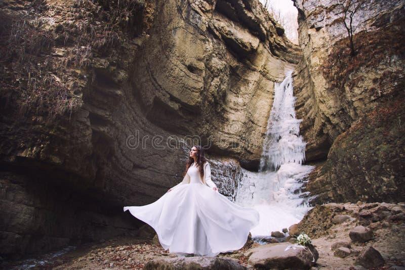 La sposa in un vestito da sposa elegante sta stando sui precedenti di un ghiacciaio fotografia stock