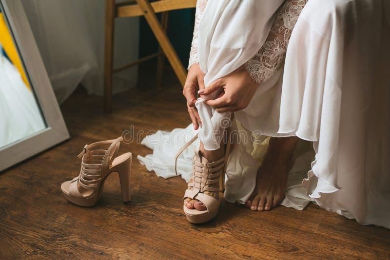 La sposa in un vestito da sposa sulla preparazione di mattina veste il bello primo piano dei sandali delle scarpe di beige Priori immagini stock