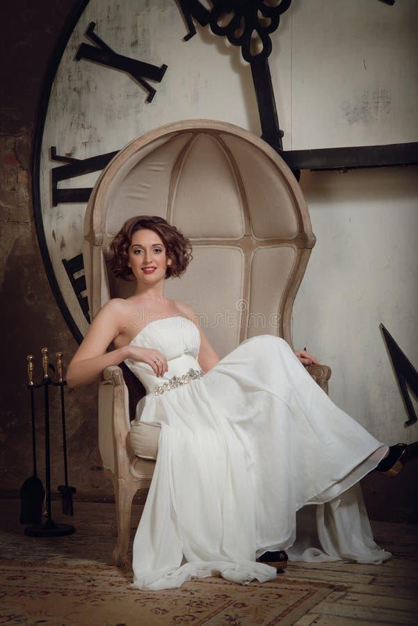 La sposa in una sedia sui precedenti degli orologi e del set di strumenti del camino Annata tonificata fotografie stock libere da diritti