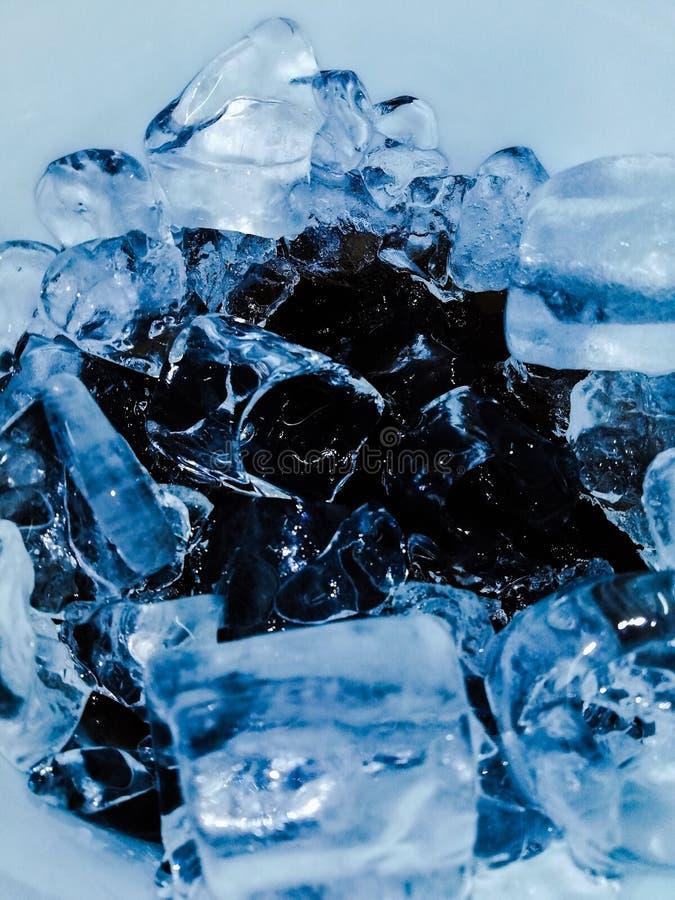 La spruzzata della cola del secchiello del ghiaccio rinfresca l'acqua nera di cristallo trasparente bianca blu immagini stock libere da diritti