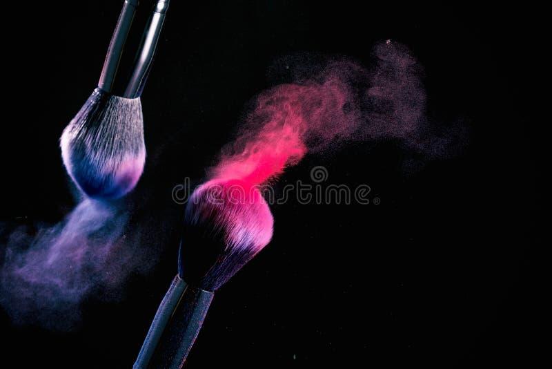 La spruzzata di polvere sulle spazzole nere di un fondo per compone su un fondo nero fotografia stock