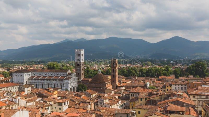 La st Martin Cathedral e torreggia le case, contro il paesaggio della montagna, a Lucca, la Toscana, Italia immagine stock libera da diritti