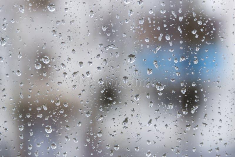 La stagione delle pioggie, gocce di pioggia sul vetro di finestra sta osservando l'orizzonte della città un giorno scuro del temp fotografie stock