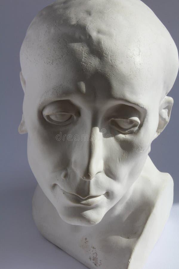 La statua bianca del gesso di uomo la testa sul fondo di grey blu immagini stock libere da diritti