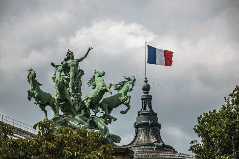 La statua bronzea ed i francesi inbandierano l'ornamento della cima grande edificio di Palais in un giorno nuvoloso a Parigi immagini stock