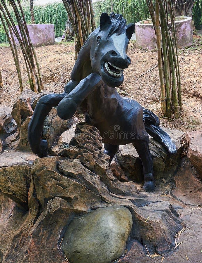 La statua del cavallo nero in un parco fotografia stock