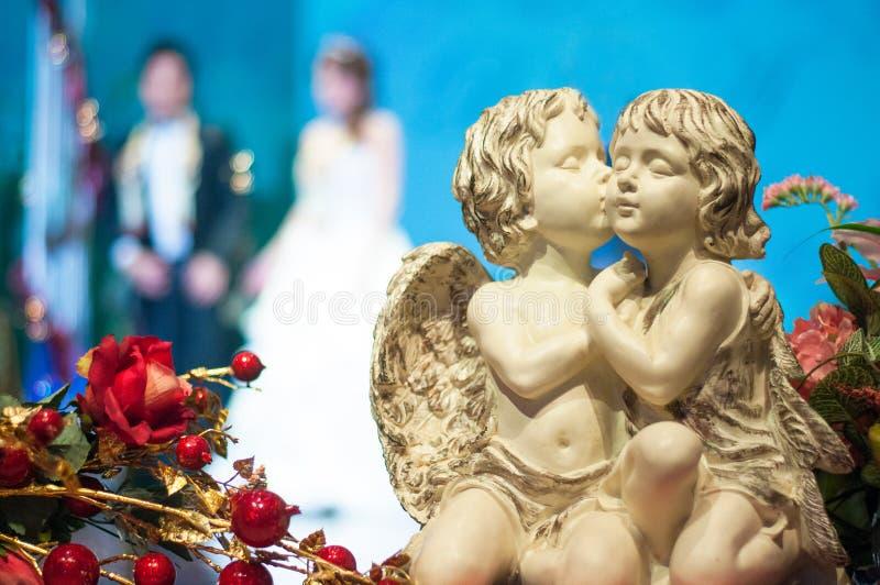 La statua del cupido ed è aumentato a cerimonia di nozze immagine stock