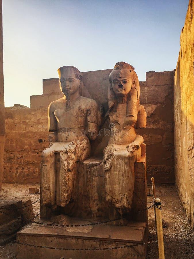 La statua del faraone e la sua moglie messa su un trono nel tempio di Luxor al tramonto L'Egitto, Luxor immagini stock libere da diritti
