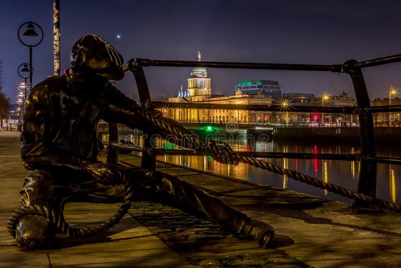 La statua del guardalinee al fiume di Liffey a Dublino alla notte, Irlanda il 20 gennaio 2017 fotografie stock