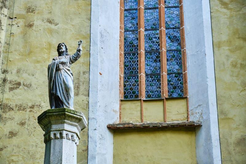 La statua del vescovo Georg Paul Binder accanto ad una finestra con il modello di vetro rotondo, vicino all'entrata in Biertan ha immagini stock