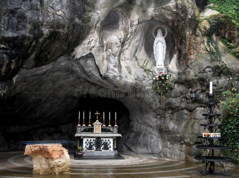 La statua di vergine Maria nella grotta di Lourdes attira molti fotografie stock libere da diritti